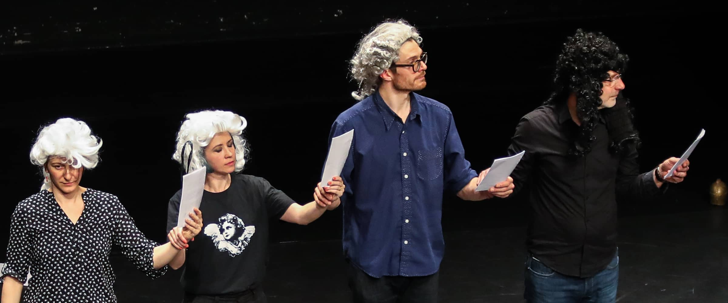 Performers wearing wigs dance with scores in their hands