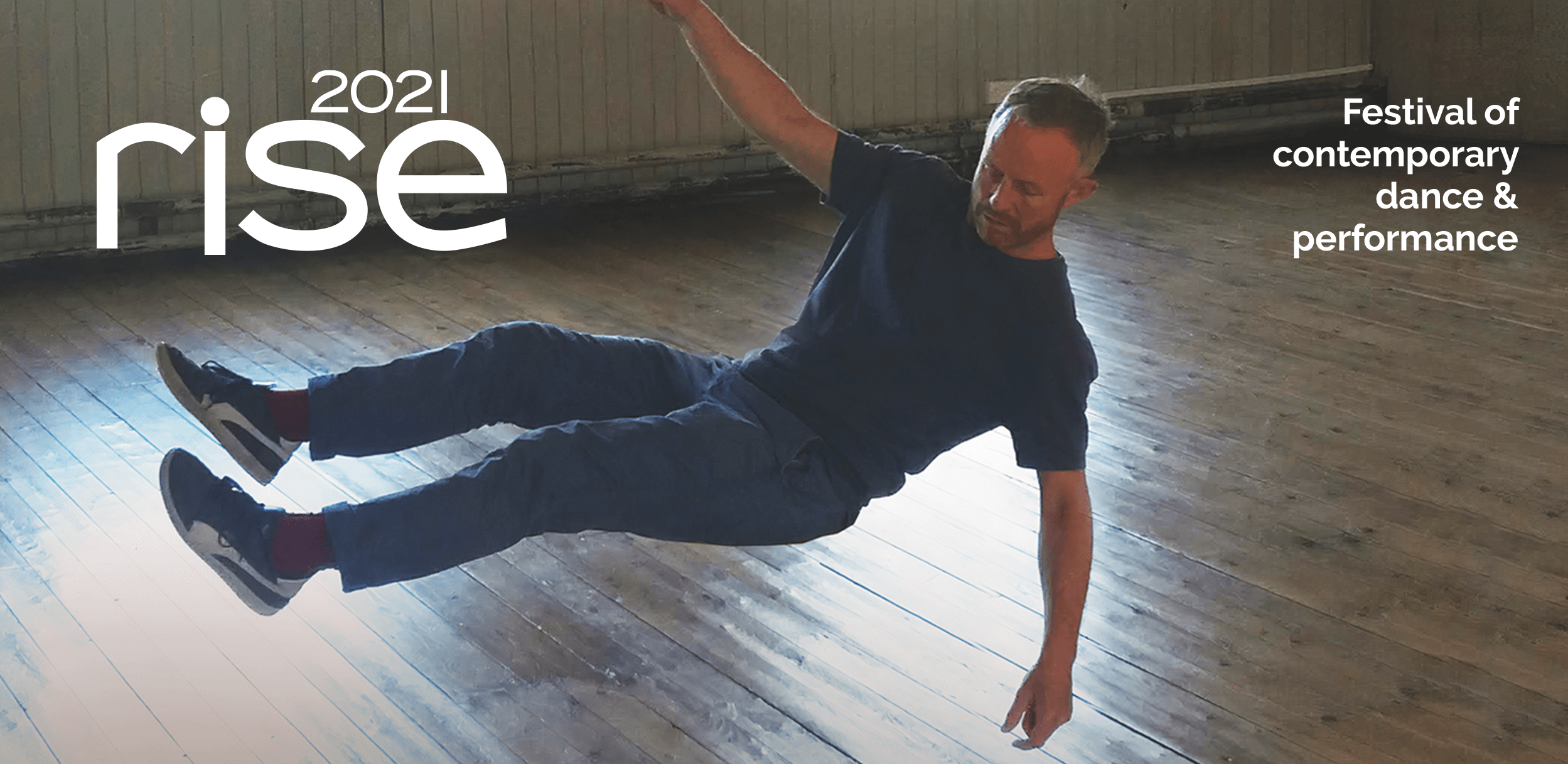 Featured dancer Charlie Morrissey is suspended in mid-air above the floor in a dance studio. Text reads: RISE 2021, festival of contemporary dance & performance.