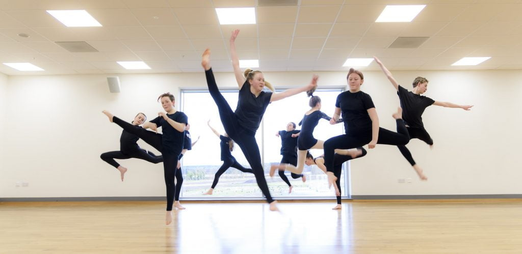 Active Schools Dance Classes in Elgin / Fochabers / Forres.10 young dancers leap in the air in a dance studio with a pale wood floor. There is a white wall behind them with a large window in the centre. All dancers are wearing black.