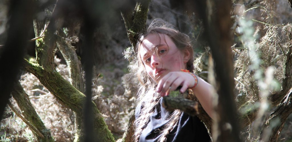 A young dancer in a black t-shirt stands in the woods amid gnarled trees and reaches toward the camera