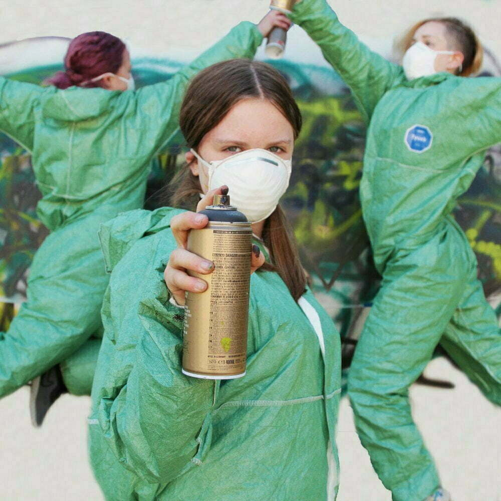 3 young dancers in green jumpsuits with facemasks and spray cans, dancing in front of graffiti on a wall