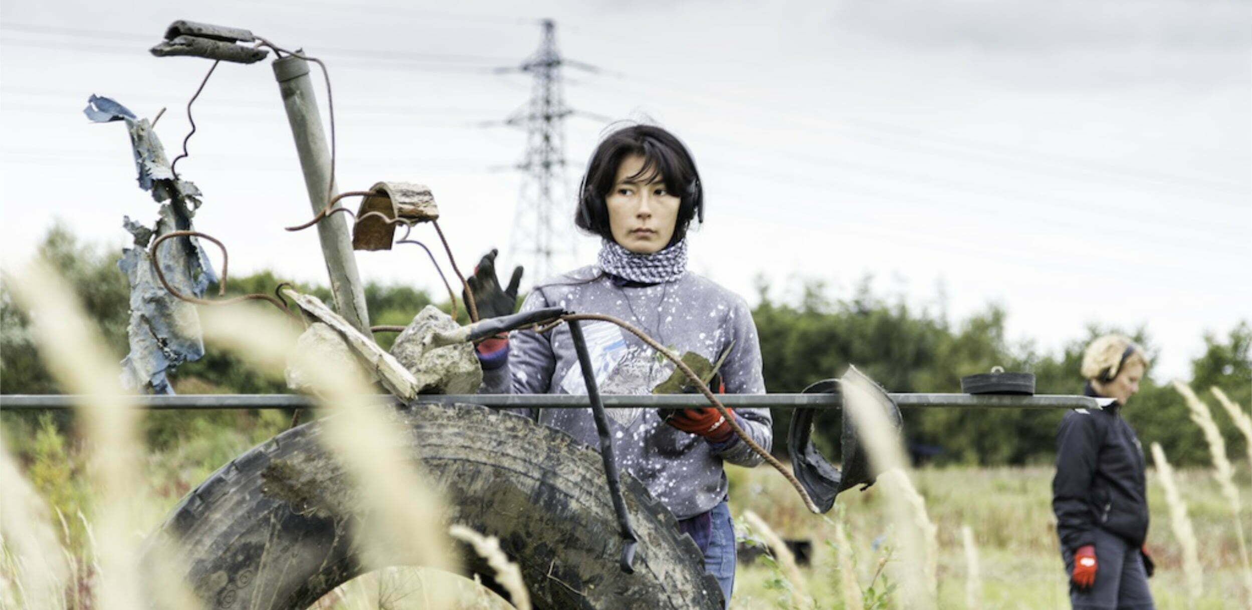 Image description: In a field, a woman wearing warm clothes, headphones and red work gloves stands facing us, one hand raised, her gaze focused to the side. Further back, another woman, also wearing headphones and gloves, walks out of the image to the right. In the foreground is a sculptural assemblage of an old car tyre, pipes and wires. In the far distance, there is a row of trees and a pylon.