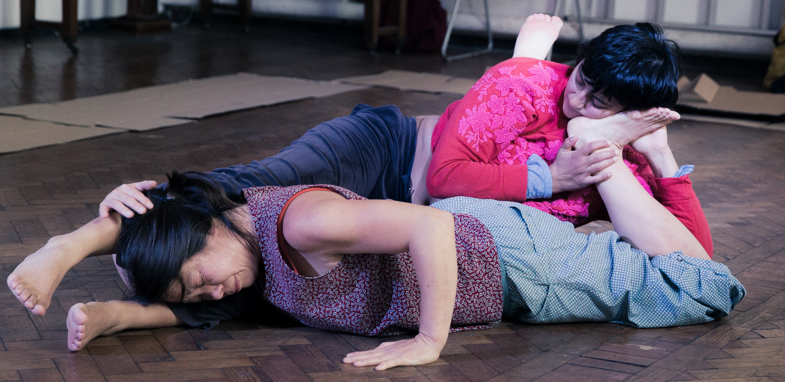 Jo Fong and Anushiye Yarnell are dancing in contact on a wooden floor. Jo is wearing a purple top and blue trousers, and facing down with one hand flat against the floor and the other wrapped around Anushiye's ankle. Anushiye is slightly above Jo, wearing a pink top and darker blue trousers. Anushiye has her face pressed against Jo's foot.