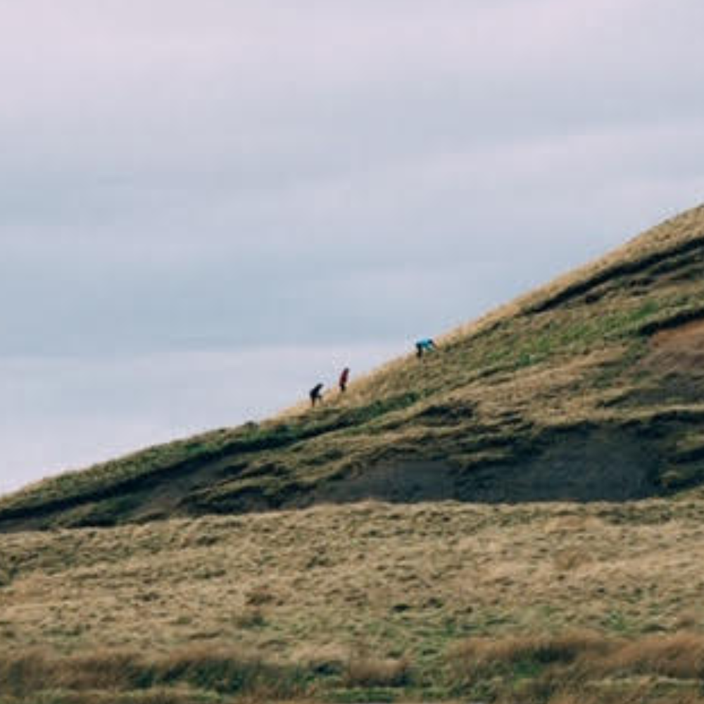 Viewed from a distance, three small figures are walking up a green hillside, which inclines upward from left to right. The figures are wearing bright waterproof jackets and are outlined against a grey, cloudy sky, which fills the upper left of the image.