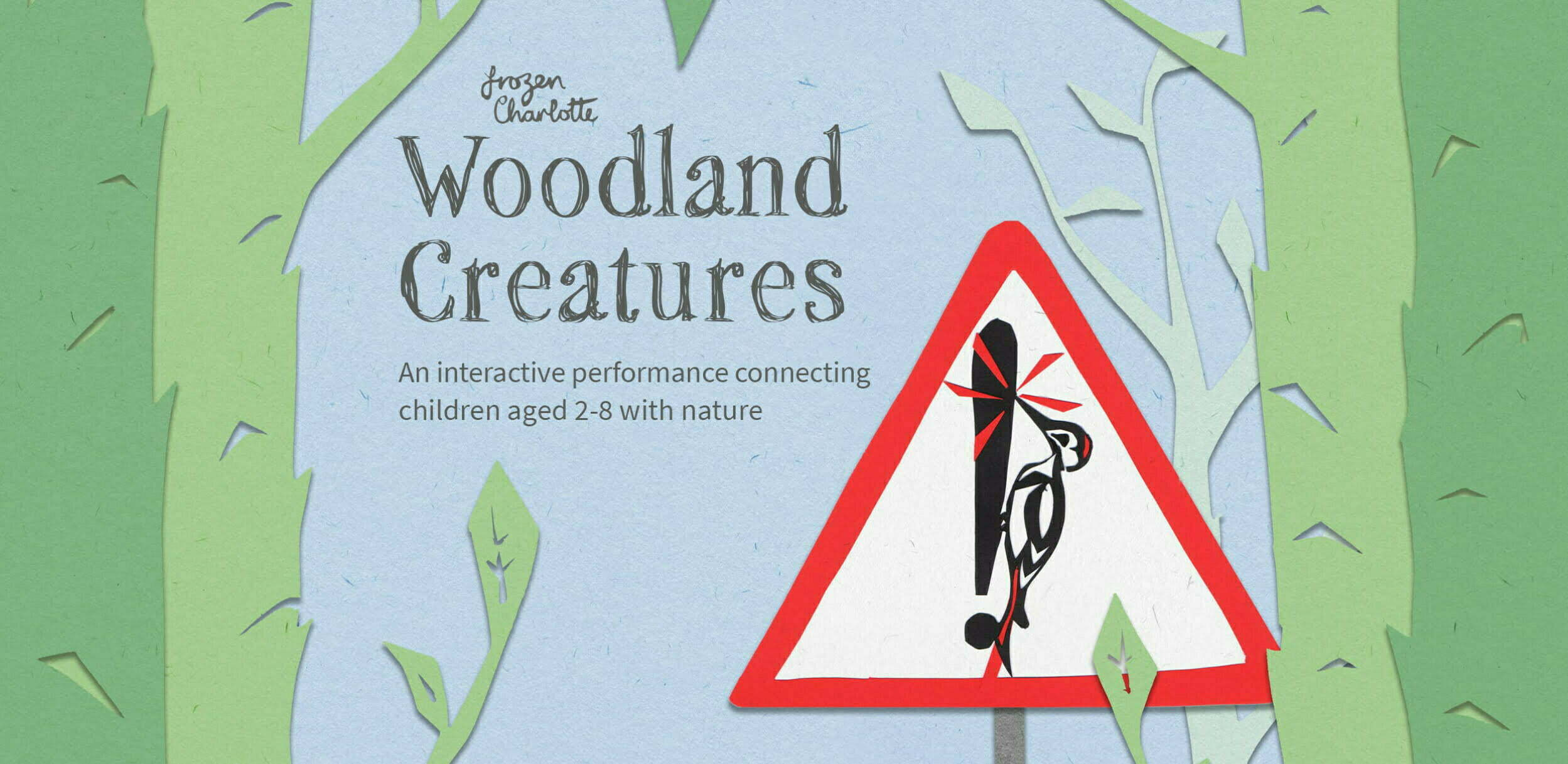 Woodland Creatures poster. A blue sky background with tall green trees on either side. Near the centre is a red and white triangle road traffic warning sign with a woodpecker pecking a black exclamation mark. Text reads: Frozen Charlotte, Woodland Creatures: an interactive performance connecting children aged 2-8 with nature.
