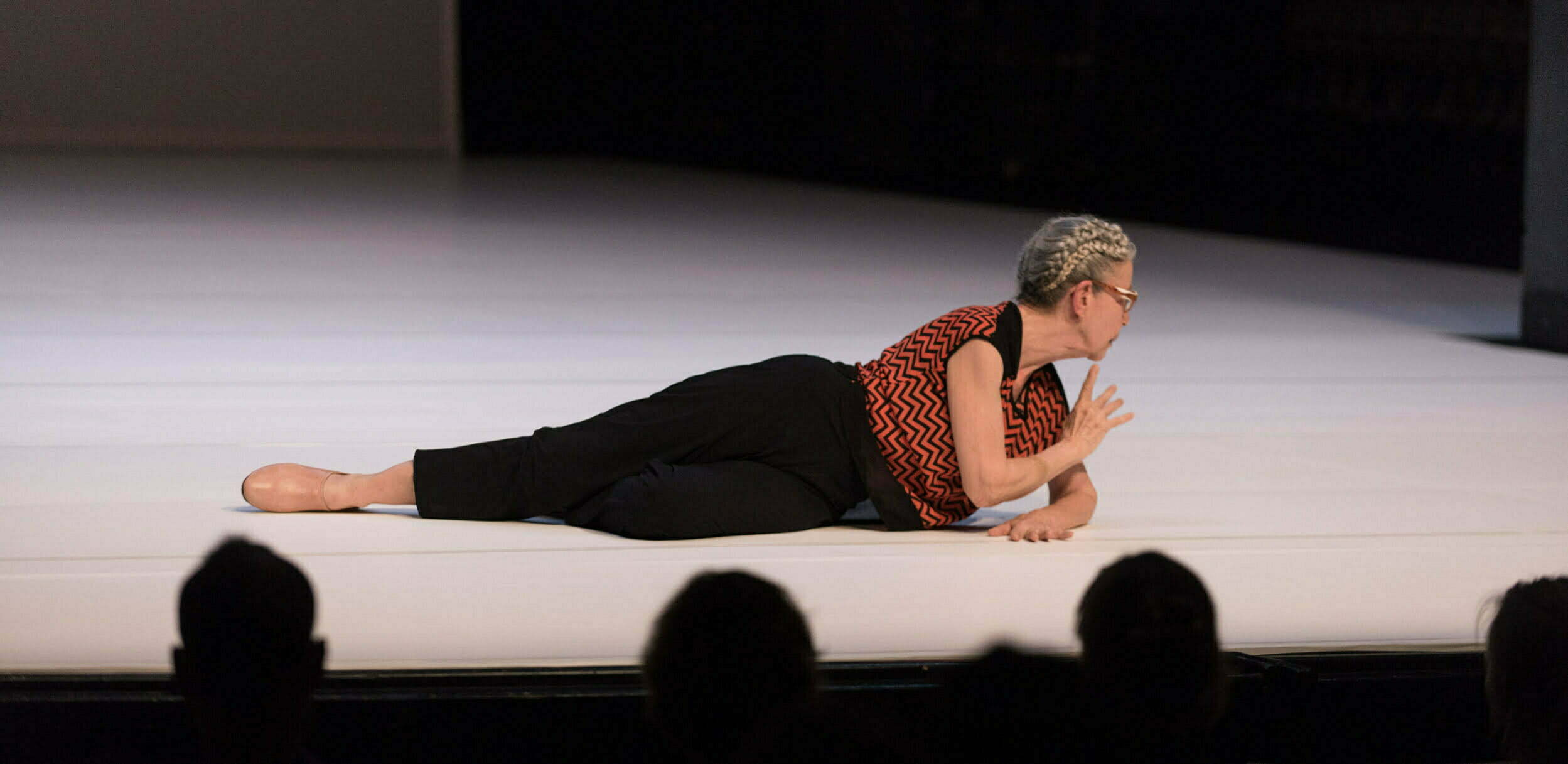 Deborah Hay lies on a white dance floor, facing to the right, with one arm supporting her and the other raised toward her chin. She is wearing dark trousers, pink shoes and an orange and black short-sleeved shirt with a zigzagg pattern. She is wearing glasses. In the foreground of the image are the silhouettes of audience members' heads, as they watch the performance.