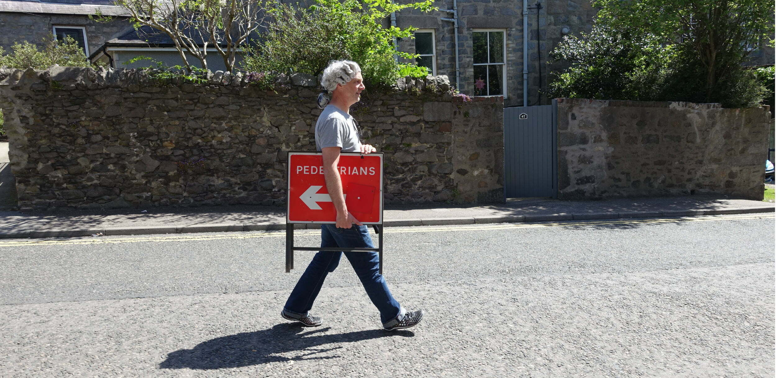 Karl Jay-Lewin walks along a public road in a residential area, from left to right. He is wearing a grey barrister's wig, a grey t-shirt and navy jeans, and he is holding a red and white roadsign with the word PEDESTRIANS and a white arrow pointing in the opposite direction to the direction he is walking. Behind him is a pavement and a grey stone wall, with a grey gate to a house and garden behind. There are tree brances and green leaves visible above the wall.